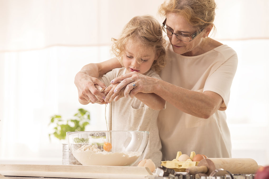 elderly woman with young girl baking